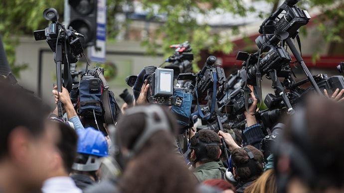 Caméras de télévision braquées sur le même objectif lors d'une manifestation.
