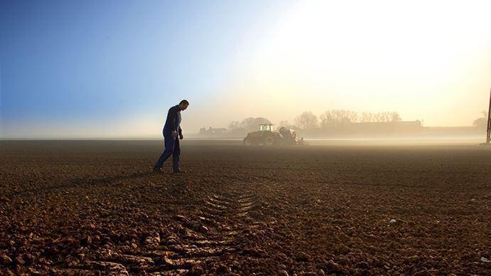 agriculteur en difficulte en train de travailler ses terres