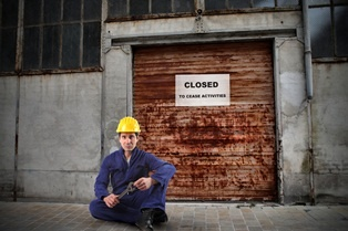 Ouvrier devant son usine fermée